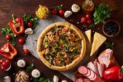 Da pizza vida ainda A peça da pizza recentemente cozida e dos seus componentes arranjou no fundo de madeira foto de stock