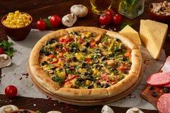 Da pizza vida ainda A peça da pizza recentemente cozida e dos seus componentes arranjou no fundo de madeira imagens de stock royalty free