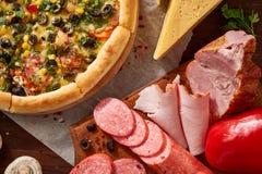 Da pizza vida ainda A peça da pizza recentemente cozida e dos seus componentes arranjou no fundo de madeira fotografia de stock
