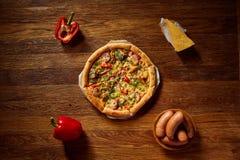 Da pizza vida ainda A peça da pizza recentemente cozida e dos seus componentes arranjou no fundo de madeira imagem de stock royalty free
