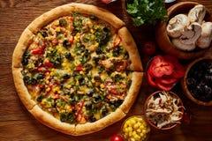 Da pizza vida ainda A peça da pizza recentemente cozida e dos seus componentes arranjou no fundo de madeira fotografia de stock royalty free