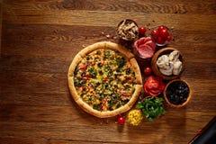 Da pizza vida ainda A peça da pizza recentemente cozida e dos seus componentes arranjou no fundo de madeira foto de stock royalty free