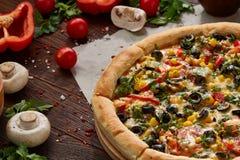 Da pizza vida ainda A pizza recentemente cozida e seus componentes arranjaram no fundo de madeira imagem de stock royalty free