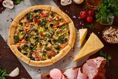Da pizza vida ainda A pizza recentemente cozida e seus componentes arranjaram no fundo de madeira imagem de stock
