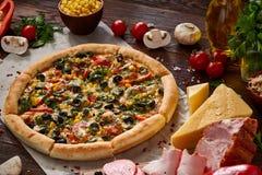 Da pizza vida ainda A pizza recentemente cozida e seus componentes arranjaram no fundo de madeira fotografia de stock royalty free