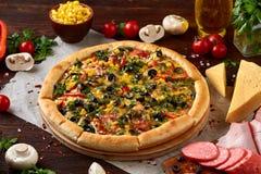 Da pizza vida ainda A pizza recentemente cozida e seus componentes arranjaram no fundo de madeira fotos de stock