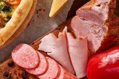 Da pizza vida ainda A pizza recentemente cozida e seus componentes arranjaram no fundo de madeira fotografia de stock