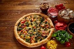 Da pizza vida ainda A pizza recentemente cozida e seus componentes arranjaram no fundo de madeira imagens de stock royalty free
