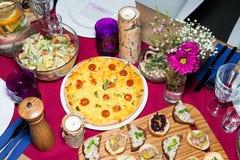 Da portare in tavola decorato per la cena La tavola meravigliosamente decorata ha messo con i fiori, le candele, i piatti ed i to Immagine Stock