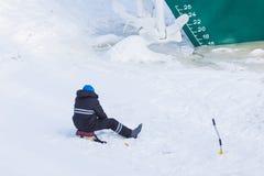 Da solo il pescatore che si siede sul ghiaccio e sulla neve del fiume di inverno sui precedenti della nave fotografia stock