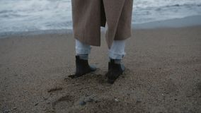 Da solo supporto della ragazza sulla costa sola con le onde di oceano spumose stock footage