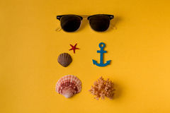 Da sopra il colpo degli occhiali da sole composti con le conchiglie su giallo Fotografia Stock Libera da Diritti