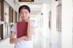 Da universidade tailandesa do estudante da porcelana de Ásia a menina bonita leu um livro Fotografia de Stock Royalty Free