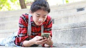 Da universidade tailandesa do estudante da porcelana de Ásia menina bonita que usa seu telefone esperto video estoque