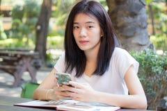 Da universidade tailandesa do estudante da porcelana de Ásia menina bonita que usa seu telefone esperto Fotografia de Stock Royalty Free