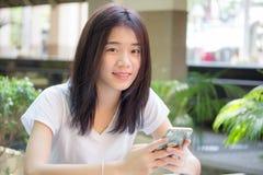 Da universidade tailandesa do estudante da porcelana de Ásia menina bonita que usa seu telefone esperto Foto de Stock Royalty Free