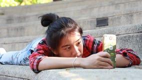 Da universidade tailandesa do estudante da porcelana de Ásia menina bonita que usa seu telefone esperto Selfie video estoque