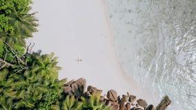 da vista 4k aérea do vertical abaixar metragem da menina que coloca em uma praia branca da areia cercada pela turquesa claro filme