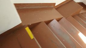 Daal onderaan bruine houten stappen in een cirkel rond de vierkante liftschacht stock footage