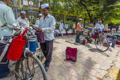 The Dabbawalas or lunch carriers wait outside the train station in Mumbai to collect lunch boxes. Dabbawalas or lunch carriers have positioned their bicycles Stock Photos