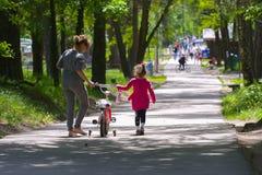 Dabushka et petite-fille montent une bicyclette en parc de ville Photo stock