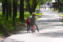 Dabushka et petite-fille montent une bicyclette en parc de ville Images libres de droits