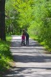 Dabushka et petite-fille montent une bicyclette en parc de ville Photos stock