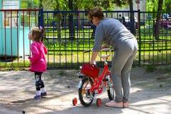 Dabushka et petite-fille montent une bicyclette en parc de ville Image libre de droits