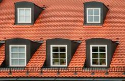 Dach der roten Fliese und giebelige Dormerfenster auf dem Aufbauen in München, Deutschland Lizenzfreie Stockfotos