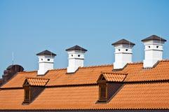 Dach der roten Fliese und weiße Kamine Stockbilder