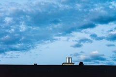 Dach mit Metallkamin und Abendhimmel mit Wolkenblaustunde Lizenzfreies Stockfoto