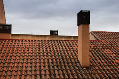 Dach mit rötlichen Fliesen und Kaminen stockfoto