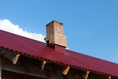 Dach mit Ziegelsteinrohr. Stockbilder