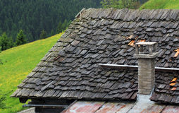 Dach von hölzernen Schindeln und von Steinkamin Stockfotografie