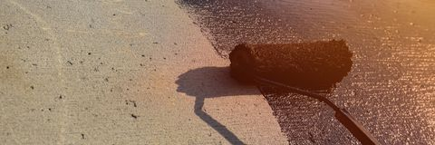 Dacharza pracownik maluje czarną węglową smołę bitum lub obrazy stock