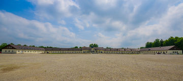 Dachau, Germania - 30 luglio 2015: Grande quadrato aperto della ghiaia dentro il sorroun del campo di concentramento, delle caser Immagini Stock