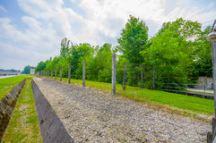 Dachau, Germany - July 30, 2015: Ditch and barbed wire fence installation around concentration camp, contrasted by Royalty Free Stock Photos