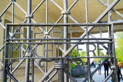 Tourists arriving defocused through wrought iron gates of Dachau. DACHAU GERMANY - SEPTEMBER 8, 2017; Tourists defocused in distance through wrought iron gates Royalty Free Stock Photography