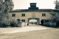 Entrance building and gates of Dachau Concertration Camp. DACHAU GERMANY - SEPTEMBER 8, 2017; Tourists looing like prisoners might have at entrance building and Stock Images