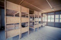 Dachau Tyskland - Juli 30, 2015: Inre sova fjärdedelar med träbritssängar som visar fångar ruskiga bosatta villkor fotografering för bildbyråer