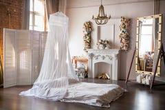 Dachboden-ähnlicher Raum mit einem Bett, einer Überdachung, einem weißen Kamin mit einer Blumenanordnung, einem weißen Schirm, ei stockfoto