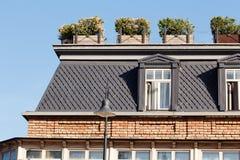 Dachbodenfenster auf dem Gebäudedach mit Blumenkästen am sonnigen Tag stockbilder