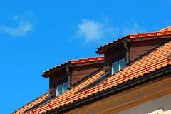 Dachbodenfenster im orange mit Ziegeln gedeckten Dach auf Hintergrund des blauen Himmels Stockbilder