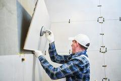 Dachdecker, der Fliese des großen Formats auf Wand installiert nach Hause zuhause Erneuerung stockfotografie
