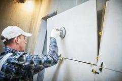 Dachdecker, der Fliese des großen Formats auf Wand installiert nach Hause zuhause Erneuerung lizenzfreie stockbilder