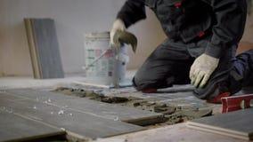 Dachdecker wendet eine Gebäudemischung auf einem Boden für Montage von Keramikfliesen, Meister steht auf Knie auf einem Boden an stock video
