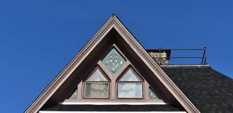 Dachowy szczyt z ciekawymi okno przeciw niebieskiemu niebu zdjęcie stock