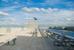 Dachspitze mit Satellitenschüssel- und Rohrzeilen Lizenzfreies Stockfoto