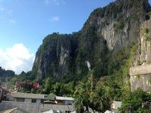 Dachspitzen zwischen großen Bergen Stockfotos