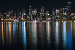 Dachte panoramische Stadtansicht der fantastischen Nachtzeit mit belichteten Wolkenkratzern über ruhiges Wasser nach lizenzfreies stockbild